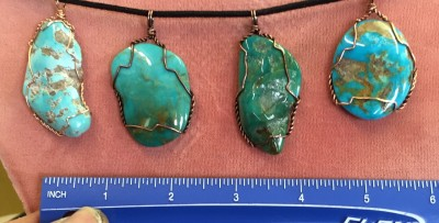 Turquoise free-form cab with some natural surface wrapped in copper wire